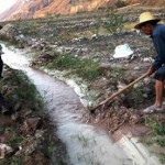 Farmers dig ditches to run water from a polluted stream into farm fields in Yunnan province, China. Photograph: Reuters